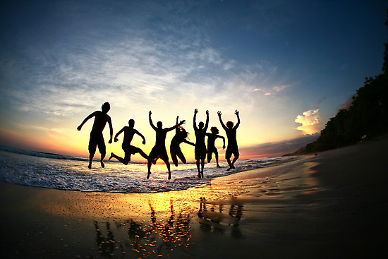 Group of Friends Jumping on Beach at Sunset by ieatstars