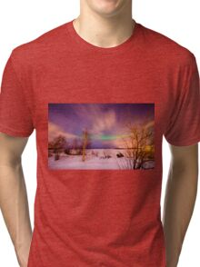 Aurora or northern lights moving across night sky in Lapland Tri-blend T-Shirt
