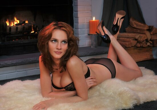 Beautiful redhead in lingerie laying in front of  fireplace by Anton Oparin