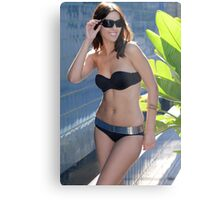 Portrait of a seductive female model in black bikini posing in front of blue wall Metal Print