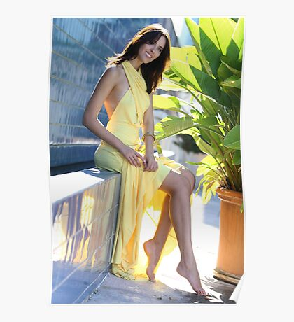 Portrait of a seductive female model in long yellow transformer dress posing in front of blue tile wall Poster