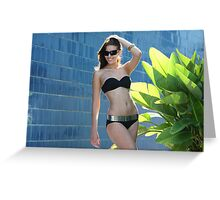 Portrait of a seductive female model in bikini posing in front of blue wall Greeting Card