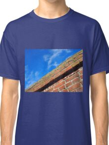 Bottom view on top of the stone wall of bricks against a blue sky Classic T-Shirt