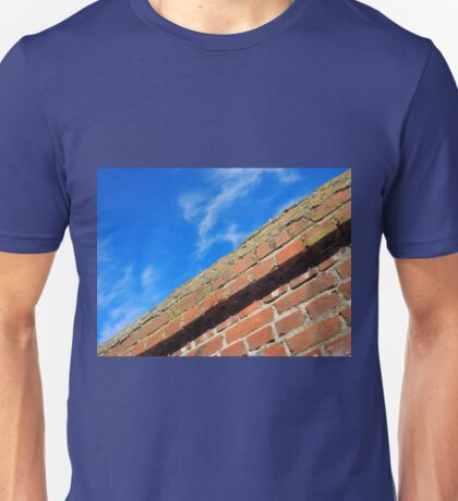 Bottom view on top of the stone wall of bricks against a blue sky Unisex T-Shirt
