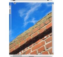 Bottom view on top of the stone wall of bricks against a blue sky iPad Case/Skin