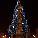 The Christmas tree behind a statue by Cosmin Roszkos