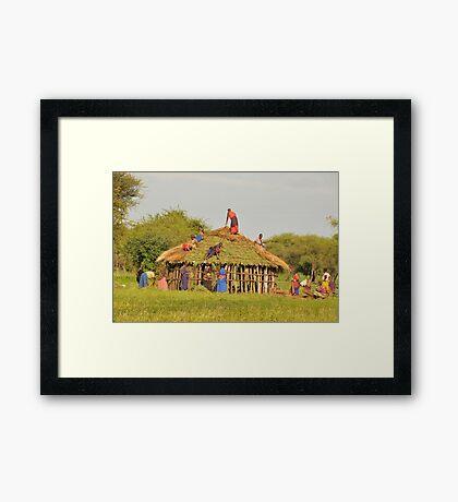 Masai women building a home in Tanzania Framed Print