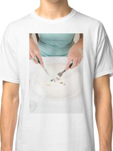 Diet concept - female Teen eats vitamins and pills with a fork and knife, instead of food  Classic T-Shirt