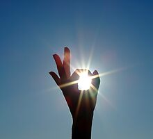 Silhouette of a female hand, the blue sky and the bright sun by Sergey Sukhorukov