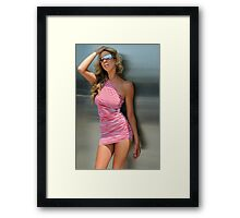 A blond woman standing in front of metallic door Framed Print