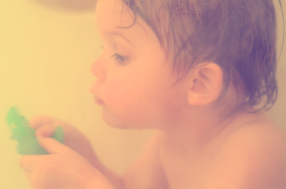Toddler at bath with alligator toy by Jason Franklin