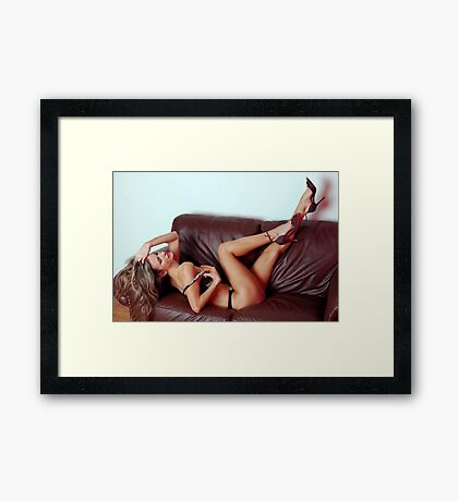 The graceful blonde in lingerie puling legs up on the leather coach  Framed Print