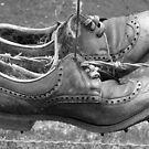 Old shoes on a fence somewhere in New Zealand by M. van Oostrum