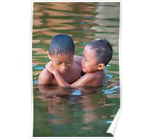 Two boys swimming in the sacred lake at sunset in Candidasa, Bali, Indonesia Poster