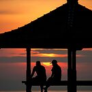Two figures in a pagoda silhouetted against the rising sun in Bali, Indonesia by Michael Brewer