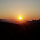 White sun with yellow halo setting over mountains in Crete by Grace Johnson