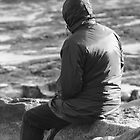 Lone Man Sitting on a Rocky Beach by Natalie Kinnear