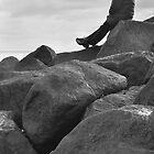 Lone Man Sitting on Rocky Beach by Natalie Kinnear