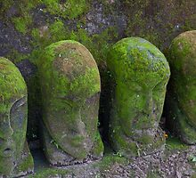 A line of green mossy stone carved heads in Batubulan, Bali, Indonesia by Michael Brewer