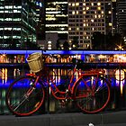 Red bike, blue river by Simon Penrose