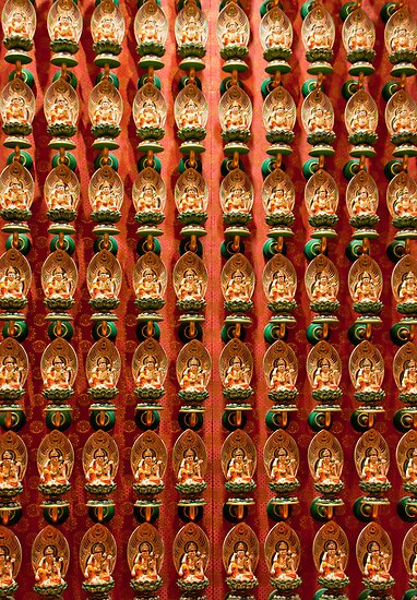 Wall of Buddhas at a Buddhist temple in Singapore by Michael Brewer