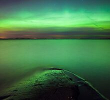 Northern lights glow over lake by Juhani Viitanen