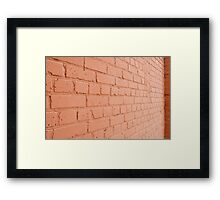 Angle view of a brick wall with a layer of red paint Framed Print