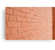 Angle view of a brick wall with a layer of red paint Canvas Print