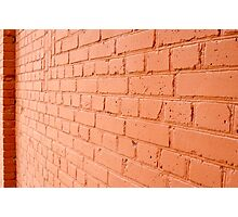 Angle view of a brick wall with a layer of red paint Photographic Print