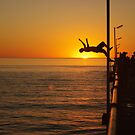 jetty jumping at sunset by janfoster