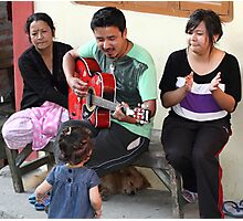 A musician entertaining his family. Photographic Print