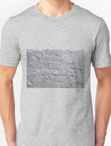 Fragment of a brick wall closeup with gray paint Unisex T-Shirt