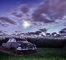 An old rusty 50's caddy in the moonlight by a cornfield by Sven Brogren