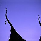 Temple roofs in the moonlight in Chiang Mai. by Phil Bower