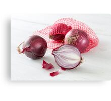 Shallots in the net on white wooden table Canvas Print