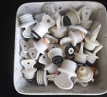 Old ceramic basin, full of hot water bottle taps -(020412)- digital photo by paulramnora