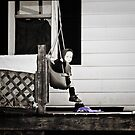 Little Amish Girl on Front Porch Swing by Marcia Rubin