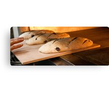 Loaves of bread in a bakery oven. Canvas Print