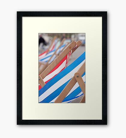 Empty deckchairs fluttering in the breeze Framed Print