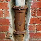 Rusty Down Pipe Framed in Red Brick by Michael Deeble