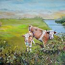 Cows and Calf eating from a hedge standing in a field on the bank of a river with distant hills by MikeJory