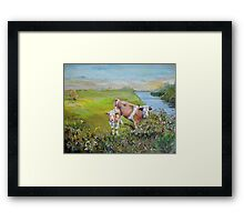 Cows and Calf eating from a hedge standing in a field on the bank of a river with distant hills Framed Print