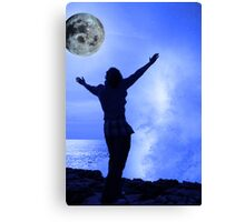 a woman with raised hands facing a wave and full moon on cliff edge Canvas Print