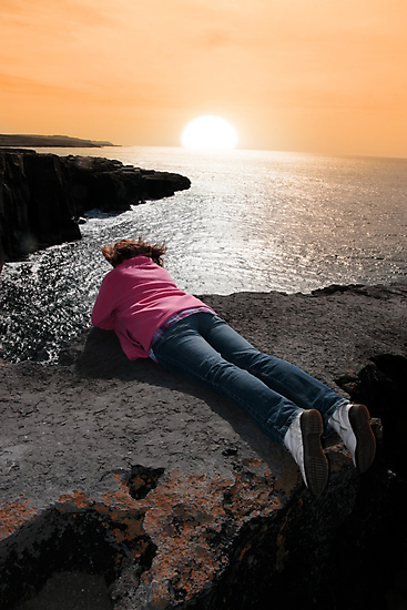 lone woman on cliffs edge by morrbyte