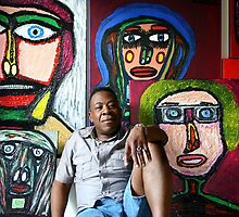 The artist Darrell Black in his studio sitting in front of his portraits by definism