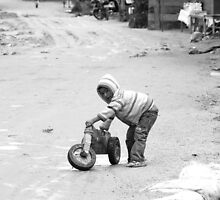 Child and his tricycle by Daniele Iengo