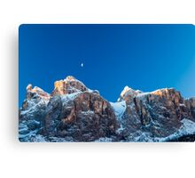 the moon is shining behind a peak Canvas Print