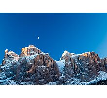the moon is shining behind a peak Photographic Print