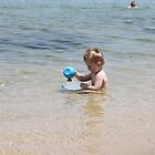 Kid playing in the sea by marolias