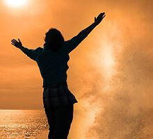 silhouette of lone woman facing a powerful wave in sunshine by morrbyte